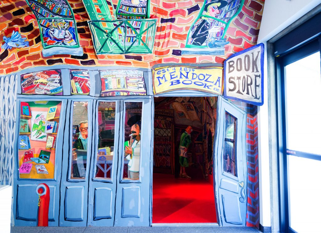 """""""The bookstore. Red Grooms. Es veu una il·lustració de l'aparador d'una llibreria."""